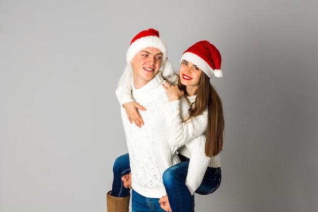 Jovem casal apaixonado celebra o natal e se diverte com chapéus de papai noel no estúdio na parede cinza