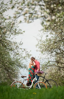 Jovem casal apaixonado com bicicletas no jardim primavera