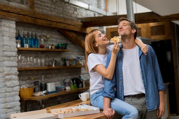 Jovem casal apaixonado comendo pizza na casa rústica