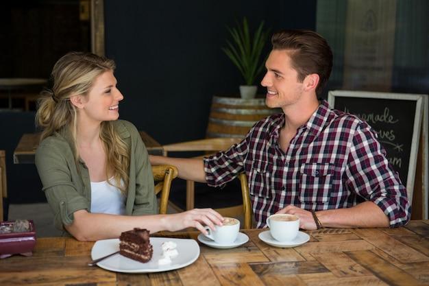 Jovem casal apaixonado conversando à mesa de um café
