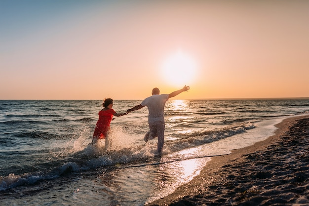 Jovem casal apaixonado corre ao longo da praia no contexto do sol poente