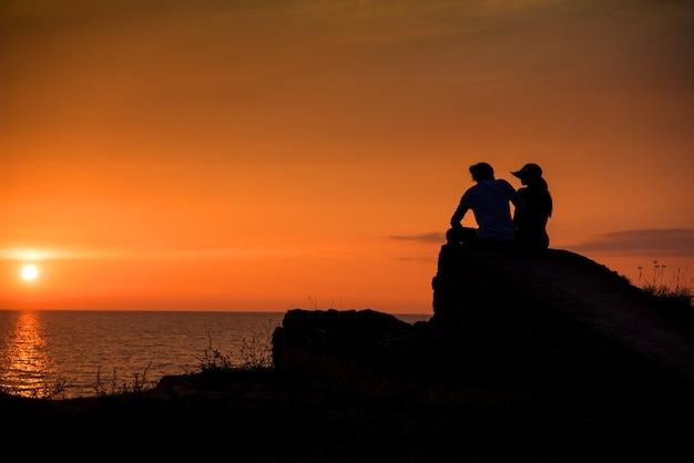 Jovem casal apaixonado curtindo o lindo pôr do sol na praia