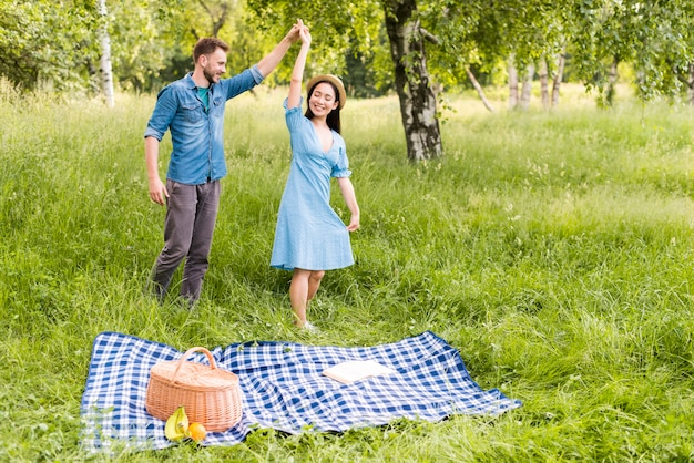 Jovem casal apaixonado dançando alegremente na zona rural