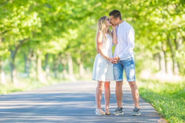 Jovem casal apaixonado, de mãos dadas e beijando-se em um dia ensolarado de verão, em pé em uma estrada rodeada por árvores verdes.