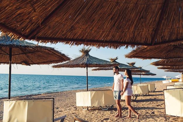 Jovem casal apaixonado, de mãos dadas entre guarda-chuvas de junco na praia do mar.