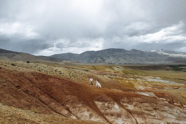 Jovem casal apaixonado de recém-casados, homem e mulher em um vale montanhoso do deserto de montanhas coloridas. noiva e noivo em vestidos de noiva