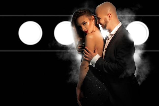 Jovem casal apaixonado de terno preto e vestido posando no estúdio na parede escura com fumaça