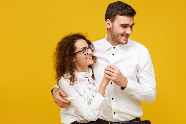 Jovem casal apaixonado, desfrutando de bons momentos juntos no primeiro encontro. homem atraente e mulher dançando, com olhares alegres, vestindo camisas brancas. conceito de união, família e relacionamentos