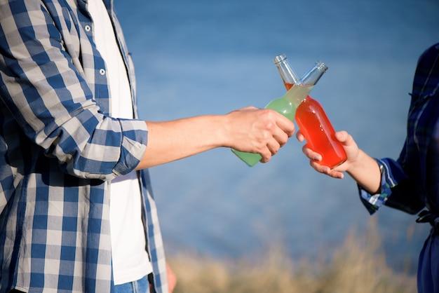 Jovem casal apaixonado, desfrutando de um cocktail na praia