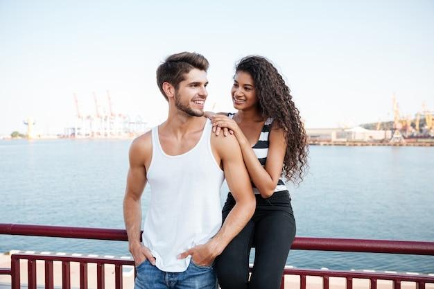 Jovem casal apaixonado e alegre em pé no porto