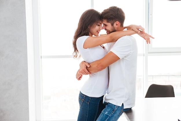 Jovem casal apaixonado e feliz em pé e se abraçando em casa