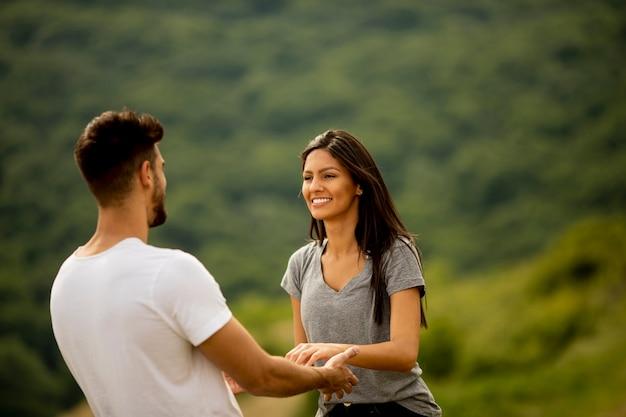 Jovem casal apaixonado e feliz no campo de grama em um dia de verão
