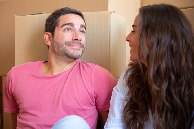 Jovem casal apaixonado e feliz sentado no chão perto de uma pilha de caixas de papelão, curtindo a mudança para um novo apartamento