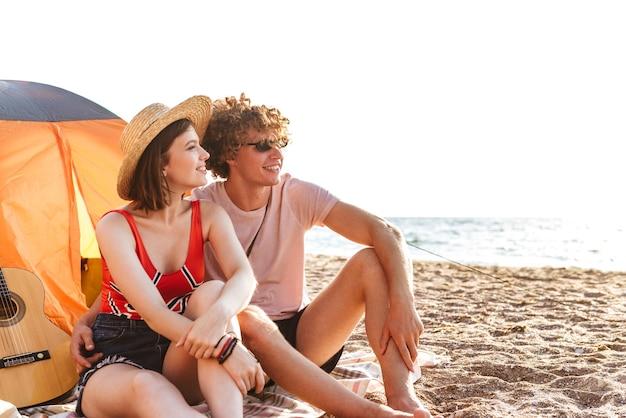Jovem casal apaixonado e fofo amigos sentados na praia ao ar livre olhando para o lado