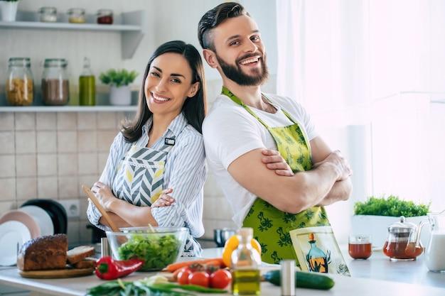 Jovem casal apaixonado e sorridente fazendo uma salada vegana super saudável com muitos vegetais na cozinha e se divertindo