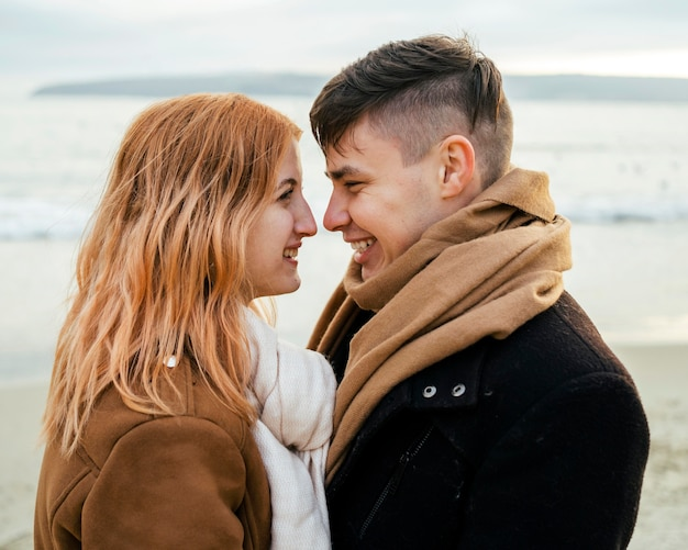 Jovem casal apaixonado e sorridente no inverno na praia