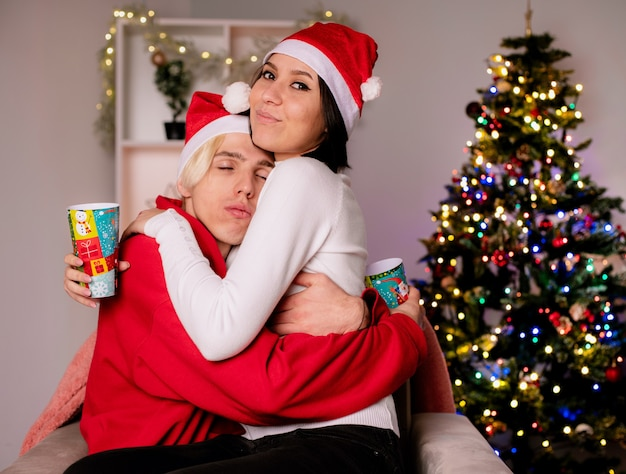 Jovem casal apaixonado em casa na época do natal com chapéu de papai noel sentado na poltrona segurando copos de plástico de natal, abraçando uma garota olhando para o cara da câmera com os olhos fechados na sala de estar