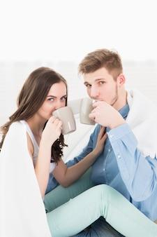 Jovem casal apaixonado em casa tomando uma xícara de café