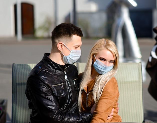 Jovem casal apaixonado em máscara médica protetora no rosto ao ar livre na rua. conceito de poluição ambiental. garoto e garota na proteção contra vírus