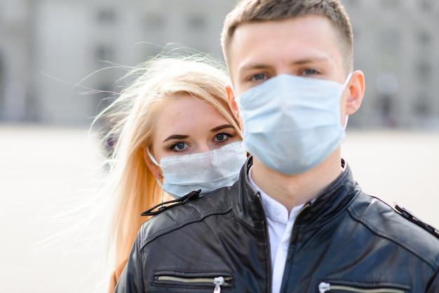 Jovem casal apaixonado em máscara médica protetora no rosto ao ar livre na rua. homem e mulher na proteção contra vírus.