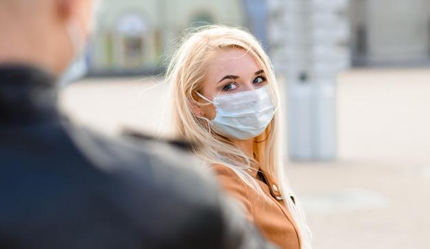 Jovem casal apaixonado em máscara médica protetora no rosto ao ar livre na rua.