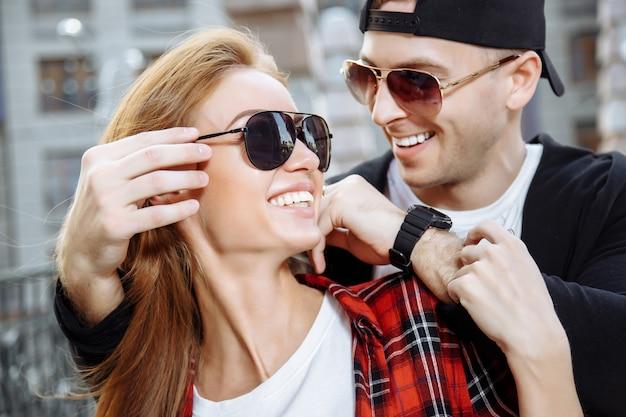 Jovem casal apaixonado em óculos de sol se divertindo juntos.