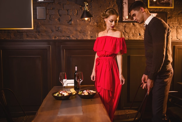 Jovem casal apaixonado em restaurante, encontro romântico