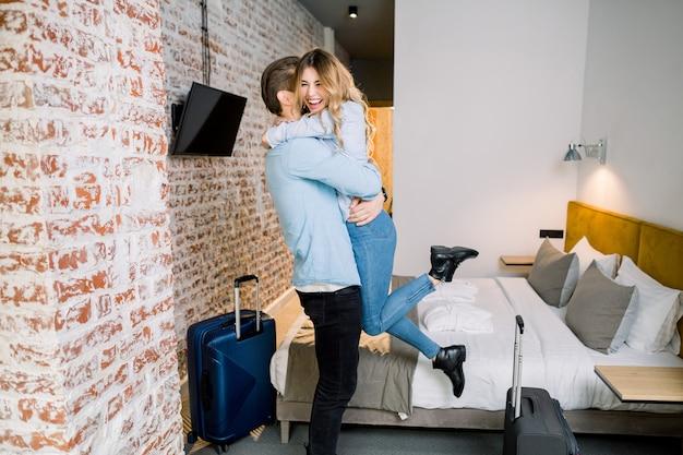 Jovem casal apaixonado em roupas casuais, passar o fim de semana romântico ou lua de mel juntos, abraçando no quarto de hotel