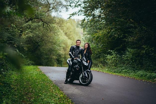 Jovem casal apaixonado em roupas de couro preto perto de uma motocicleta esportiva preta na estrada