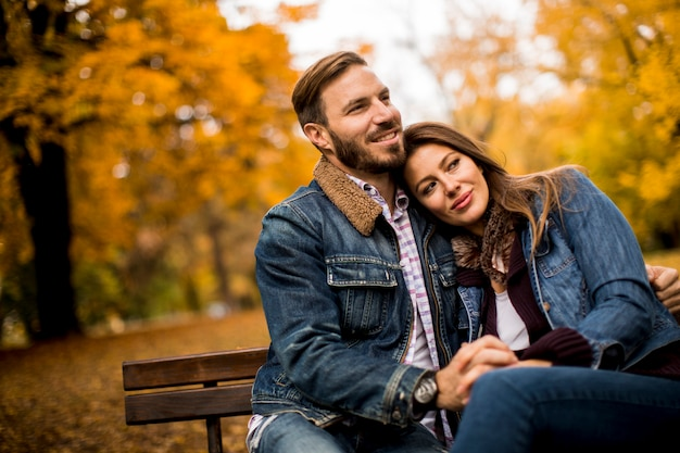 Jovem casal apaixonado em um banco no parque outono