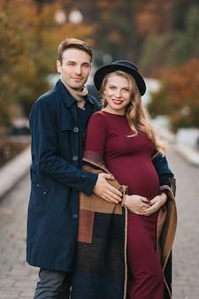 Jovem casal apaixonado em um outono parque da cidade feliz homem elegante e linda mulher grávida ...