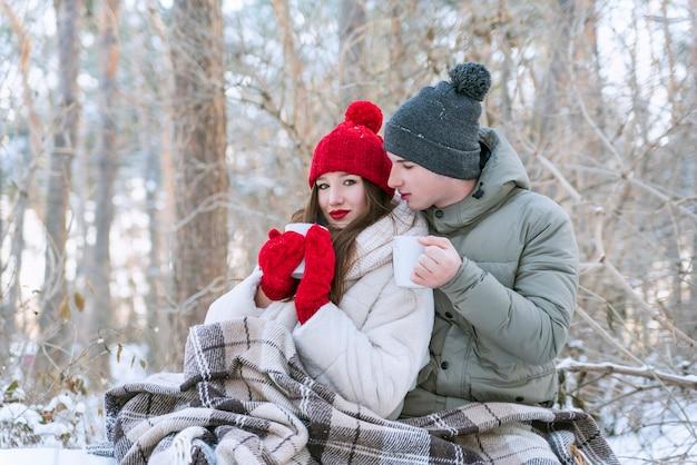 Jovem casal apaixonado em winter park, embrulhado em cobertor e bebe chá. história de amor.