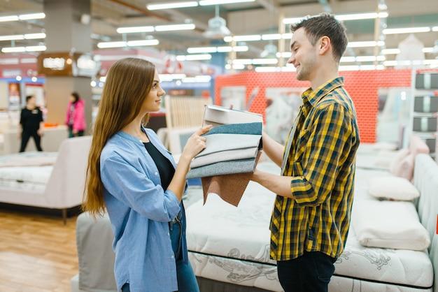 Jovem casal apaixonado, escolhendo a textura do colchão no showroom da loja de móveis. homem e mulher procurando amostras de quarto em uma loja, marido e mulher compram produtos para interiores modernos