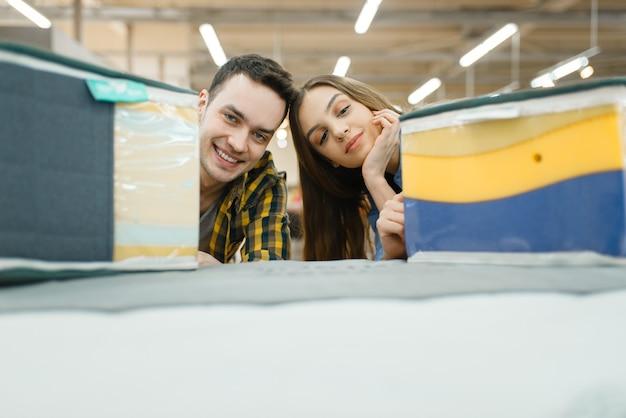 Jovem casal apaixonado, escolhendo o colchão para a cama no showroom da loja de móveis. homem e mulher procurando amostras de quarto em uma loja, marido e mulher compram produtos para interiores modernos