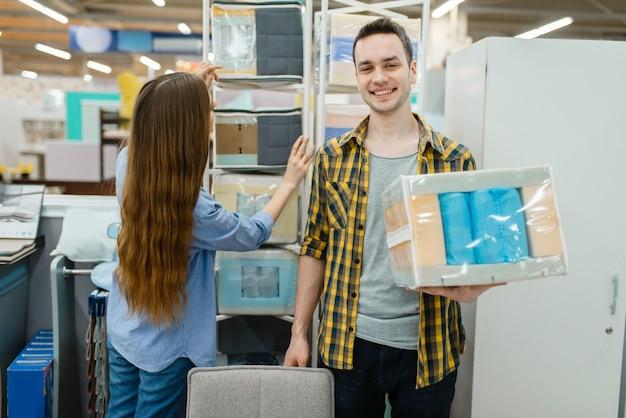 Jovem casal apaixonado, escolhendo o núcleo do colchão no showroom da loja de móveis. homem e mulher procurando amostras de quarto em uma loja, marido e mulher compram produtos para interiores modernos