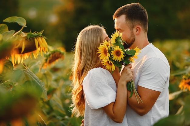 Jovem casal apaixonado está se beijando em um campo de girassol. retrato de casal posando no verão em campo.