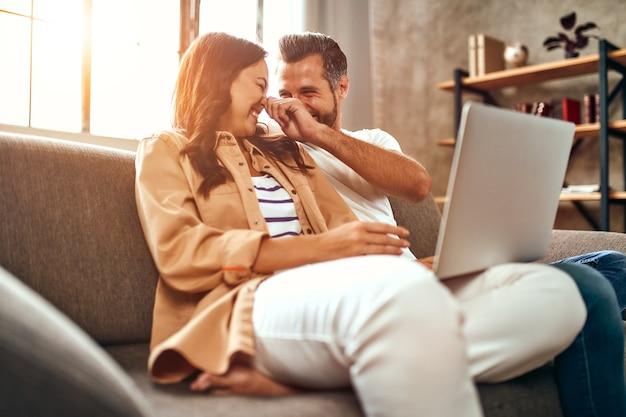 Jovem casal apaixonado está sentado no sofá com um laptop em casa. um casal está relaxando e se divertindo na sala de estar. compras online, trabalhe em casa.