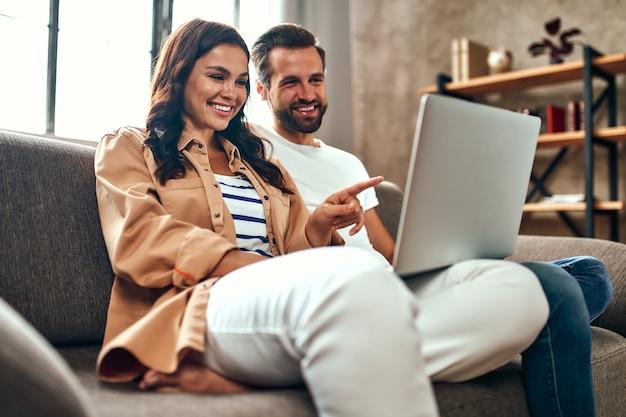Jovem casal apaixonado está sentado no sofá com um laptop em casa. um casal está relaxando na sala de estar. compras online, trabalhe em casa.