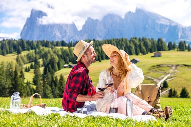 Jovem casal apaixonado fazendo piquenique visitando dolomidades nos alpes