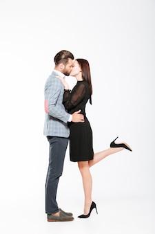 Jovem casal apaixonado feliz beijando isolado