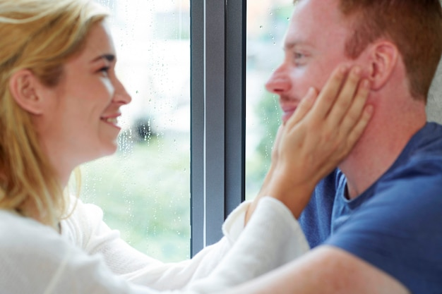 Jovem casal apaixonado ficando em casa em dia chuvoso tocando rostos e se olhando foc ...