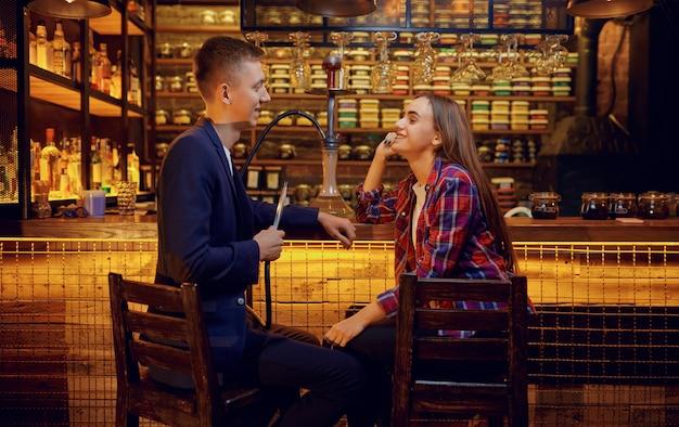 Jovem casal apaixonado fuma no balcão de um bar de narguilé, relaxando