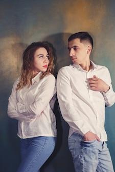 Jovem casal apaixonado, homem e mulher, está ofendido e olhando um para o outro