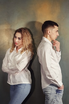 Jovem casal apaixonado, homem e mulher, ofendem-se e ninguém quer se aguentar, eles ficam de costas um para o outro contra a parede, tonificados.