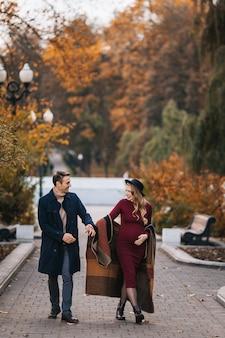 Jovem casal apaixonado, homem feliz e sua esposa grávida, de mãos dadas e andando por um parque em um s ...