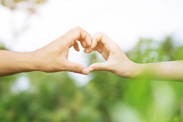 Jovem casal apaixonado mostra de mãos dadas forma de coração