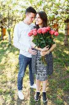 Jovem casal apaixonado, mulher segurando flores, feliz e apreciar a bela natureza