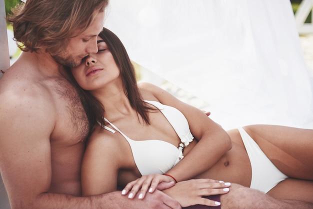 Jovem casal apaixonado na areia num dia de verão na praia.