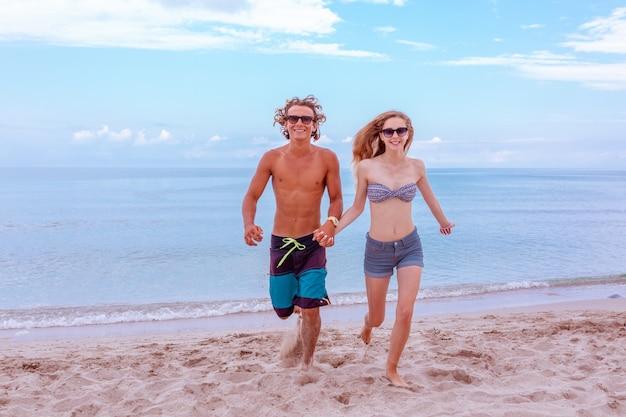 Jovem casal apaixonado na praia e aproveitando o tempo juntos, correndo na praia