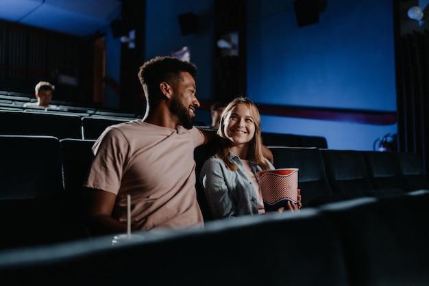 Jovem casal apaixonado no cinema, assistindo filme.